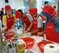 Ajinomoto staff and the children struggle in the cooking competition that required preparing 2 main recipes.